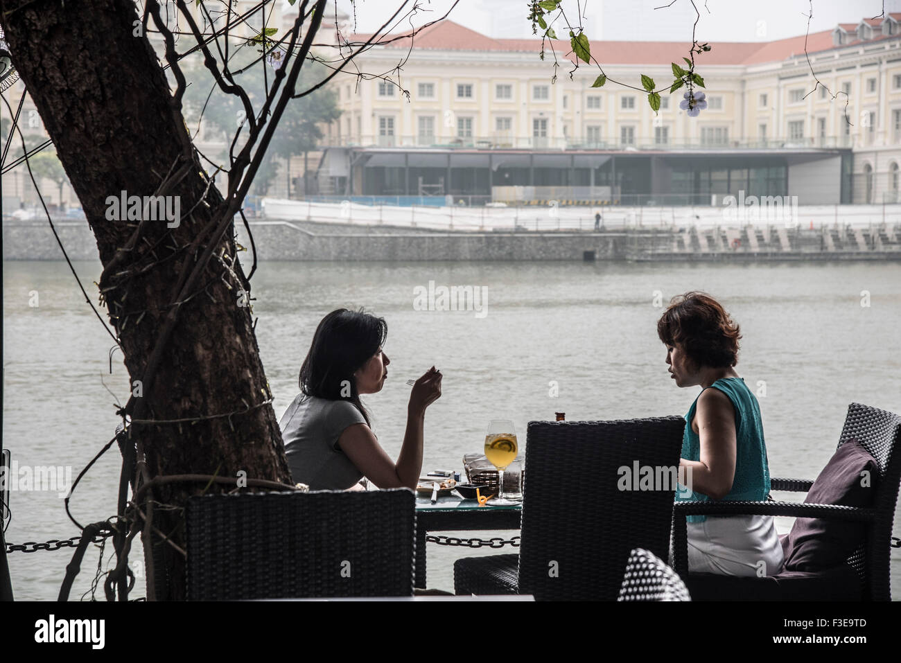 Two women friends have lunch outdoors under hazardous haze pollution levels of more than 200 PSI in Singapore, due - Stock Image