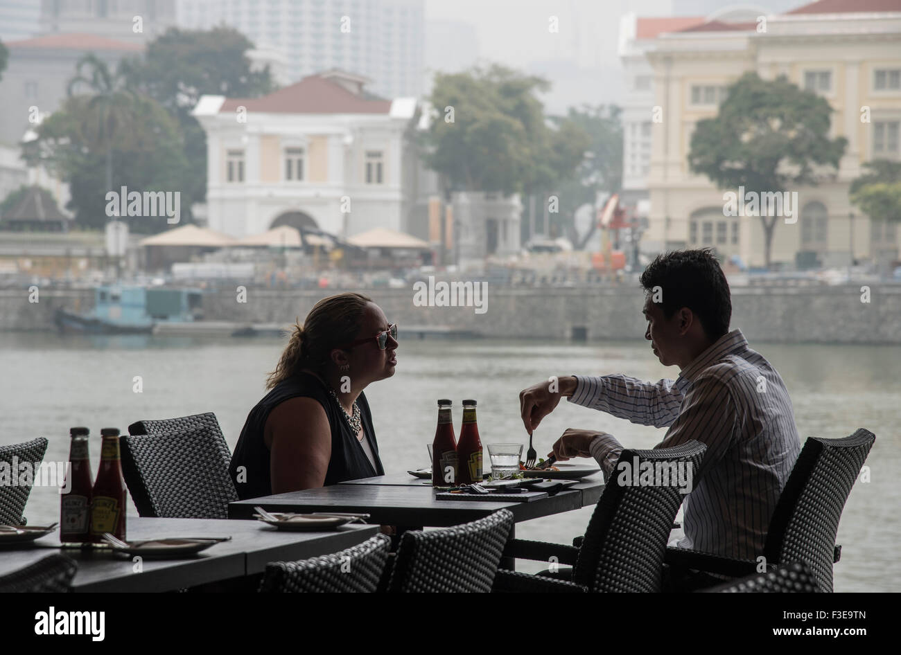 Couple have lunch outdoors under hazardous haze pollution levels of more than 200 PSI in Singapore, due to destruction - Stock Image
