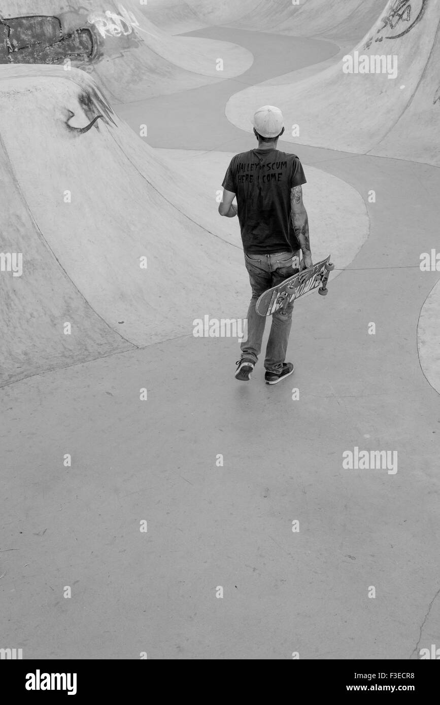rear view of mature adult walking with skateboard inside skate park - Stock Image