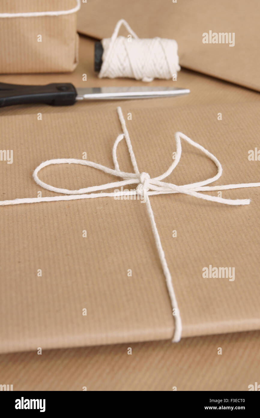 Parcel packing with brown parcel paper and string - Stock Image
