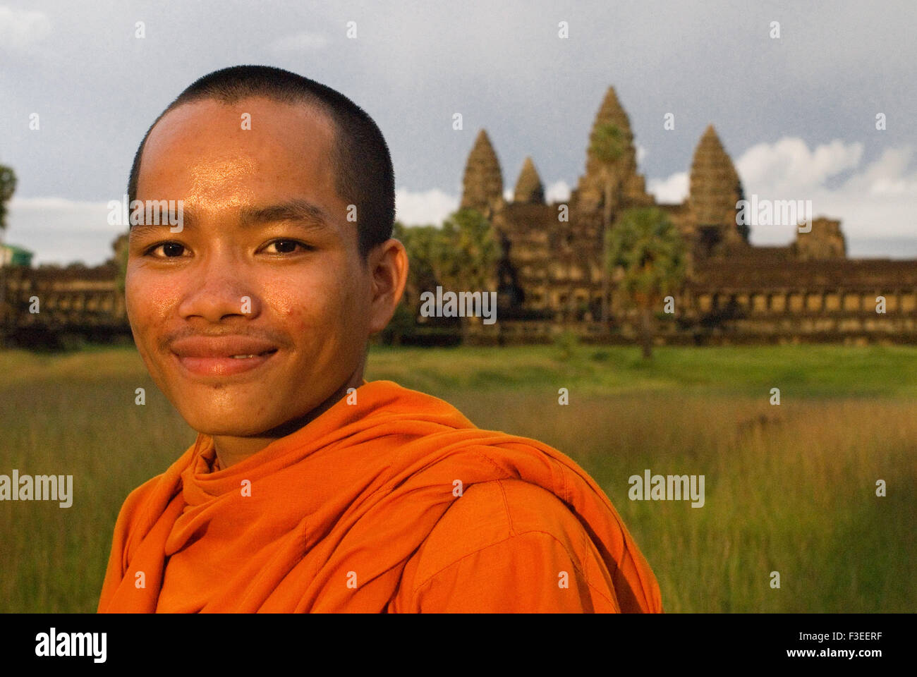 Buddhist monk on the outside of the Temple of Angkor Wat. Angkor Wat, the largest monument of the Angkor group and - Stock Image