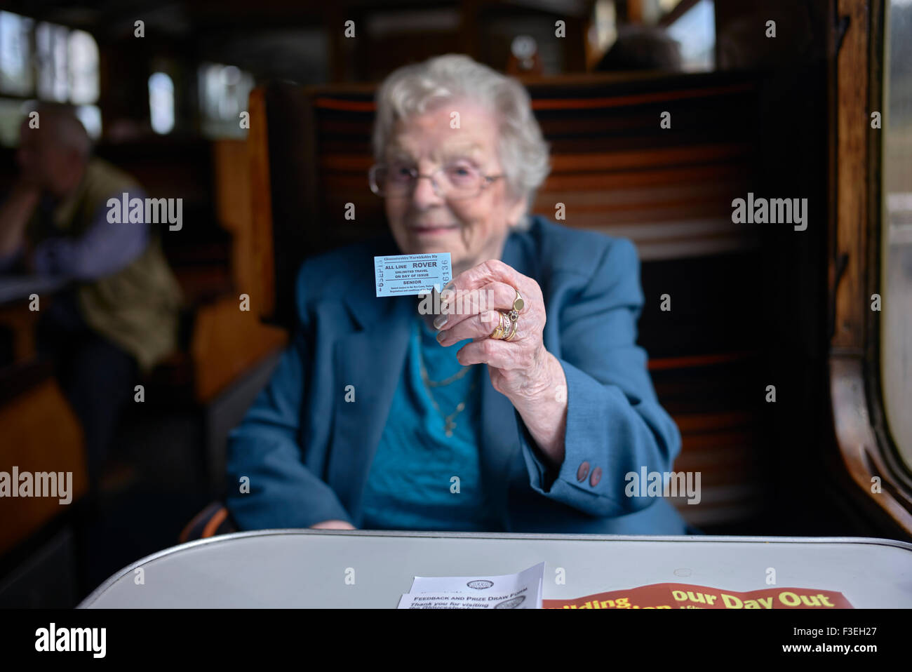 Senior citizen displaying all day rail ticket aboard the GWR preserved rail service at Toddington Gloucestershire - Stock Image