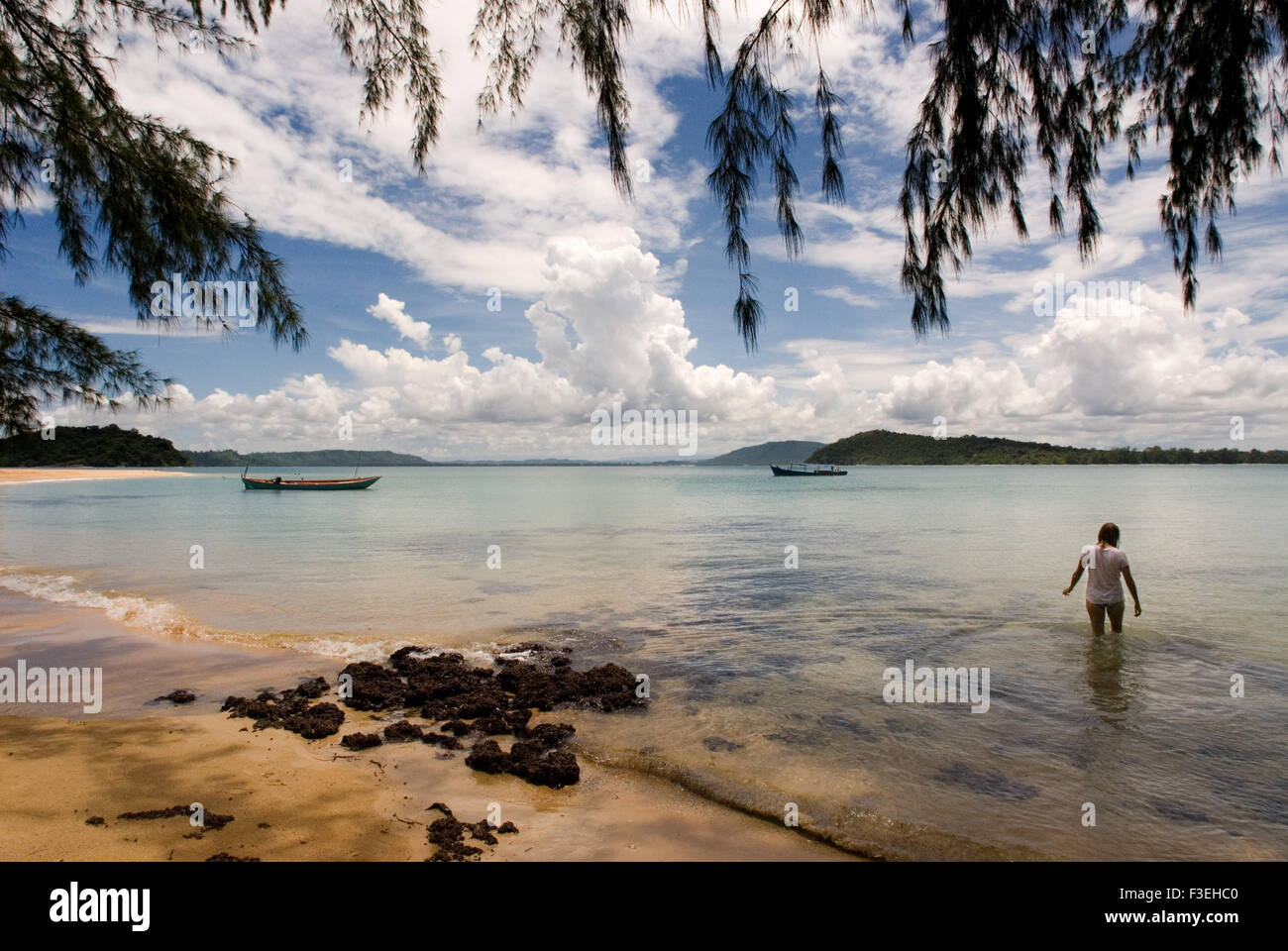 Swimming at the beach on the island of Koh Russei. Koh Russei is still living under the shadow of its former self, - Stock Image