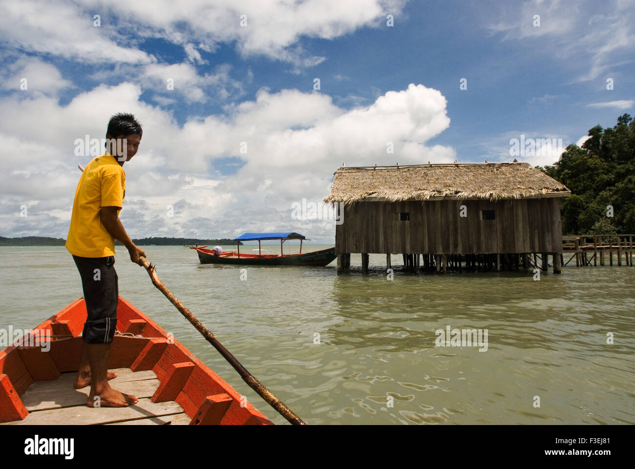 Hut in the Ream National Park. A red boat approaches. Ream National Park is 18 kilometres from downtown Sihanoukville, towards P Stock Photo