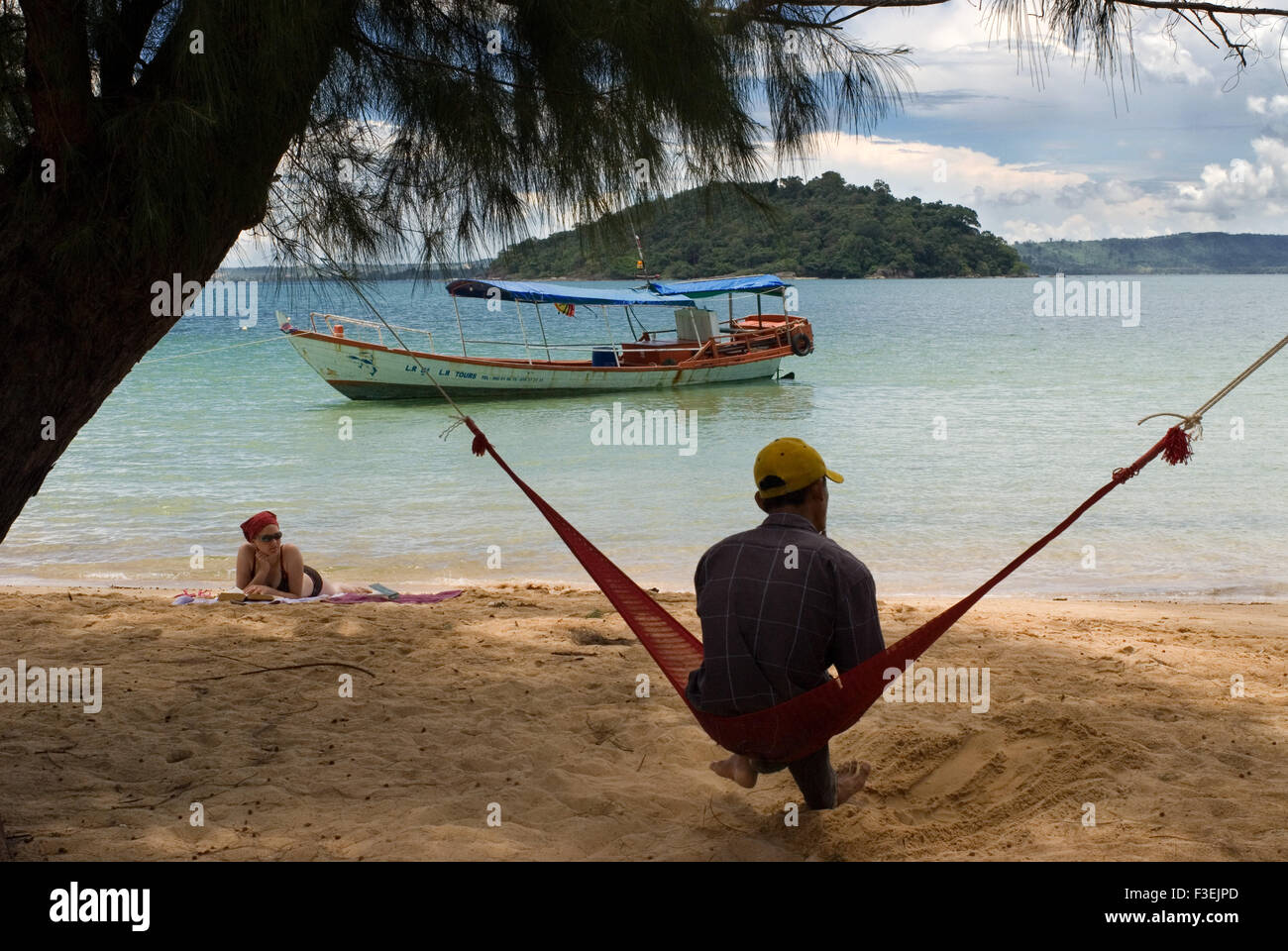 Lying in a hammock on the sea shore of the island of Koh Russei. Koh Russei (or Bamboo Island as it's commonly known) Stock Photo