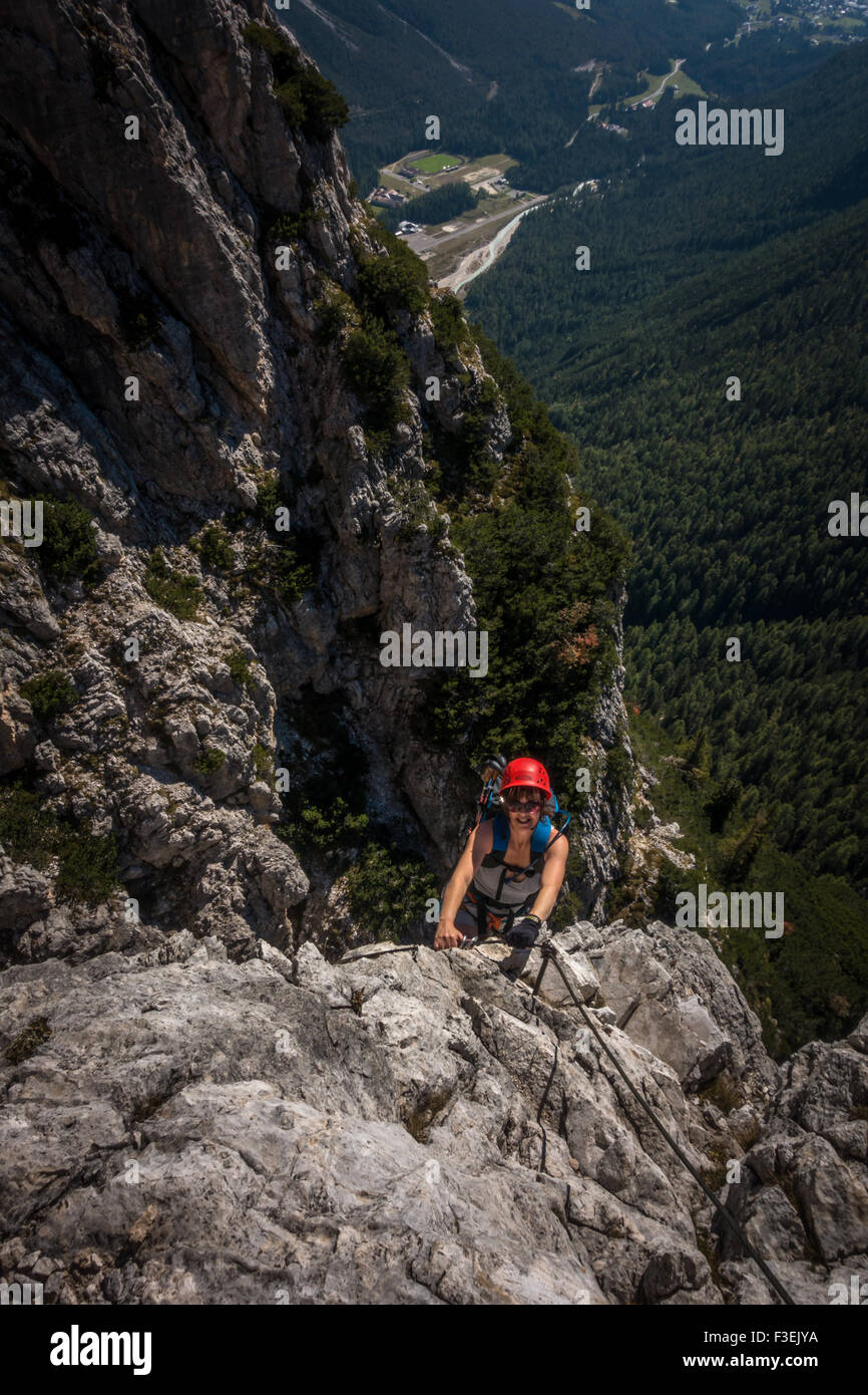 Climber on the Ettore Bovero via ferrata, looking towards Cortina in the valley from Col Rosa,  (Dolomites, Italy) - Stock Image