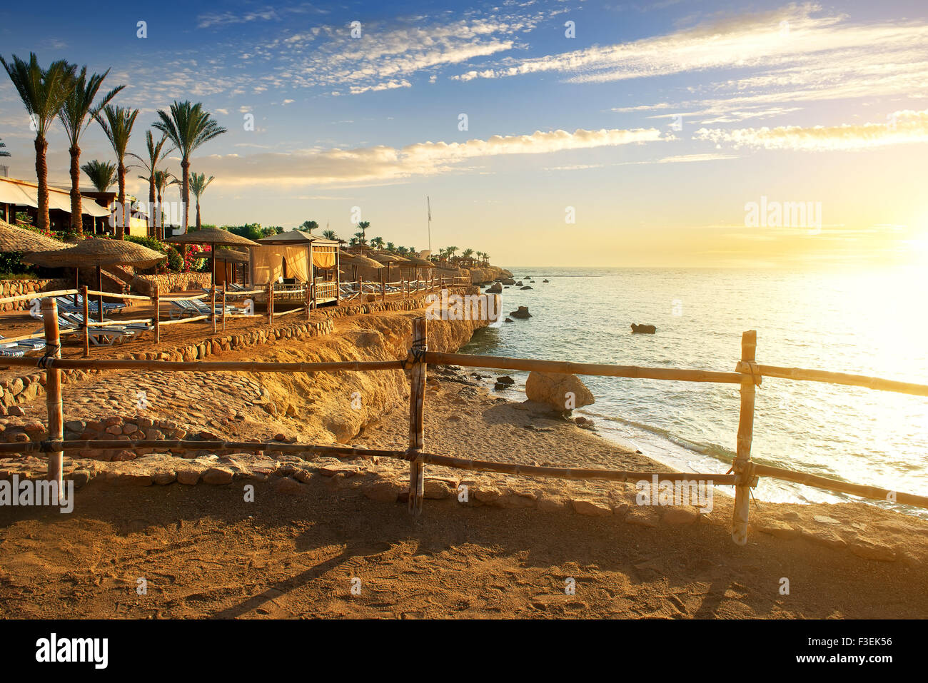 Sandy beach in egyptian hotel at sunset - Stock Image