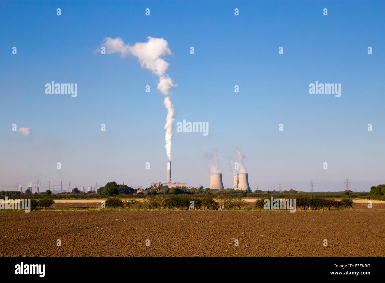 Stock photograph of Cottam power station with steam / smoke emissions rising into the sky from the cooling towers. - Stock Image