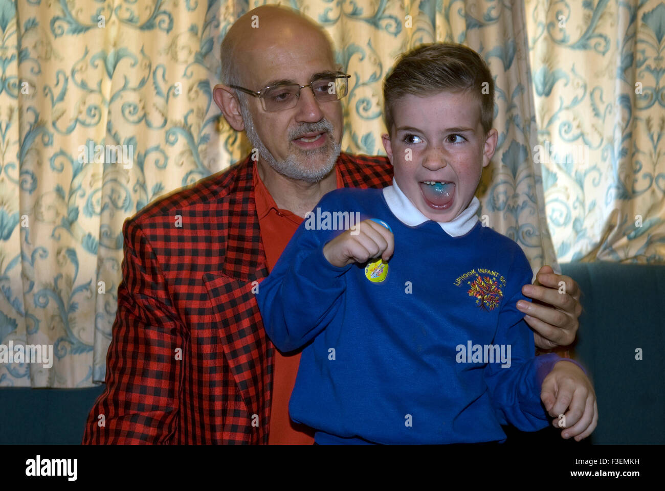 Youngster having fun with a magician at a Macmillan Cancer Care fundraising day, Liphook, Hampshire, UK. Stock Photo