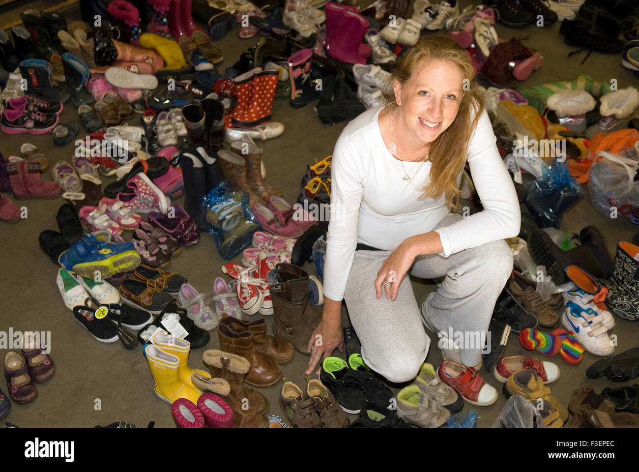 Co-founder of an appeal for donations to help refugees fleeing war torn Syria surrounded by some of the donated - Stock Image