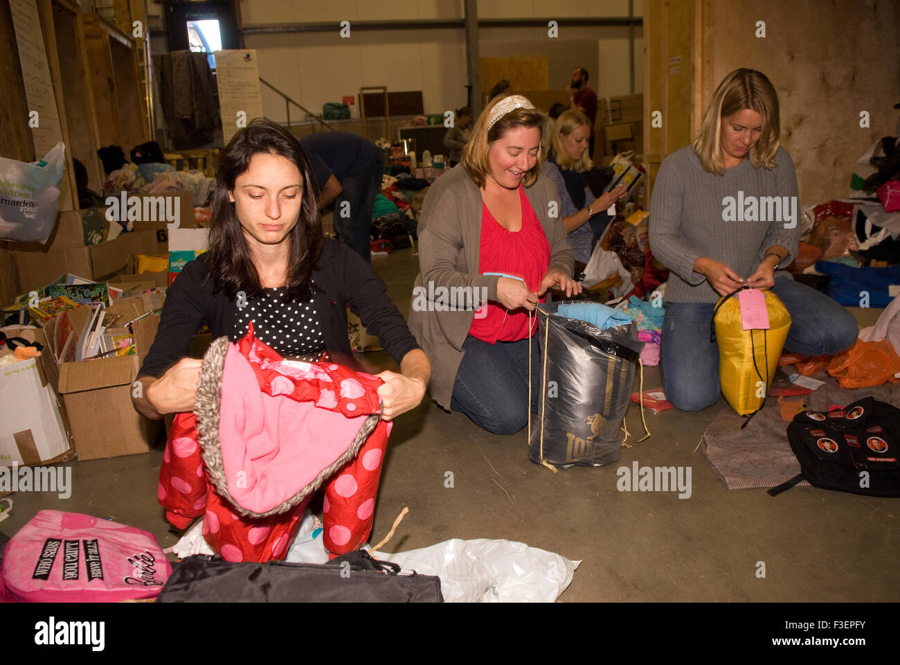 Volunteers in a shipping company's warehouse packing up donated items of clothing and other non-perishable items - Stock Image