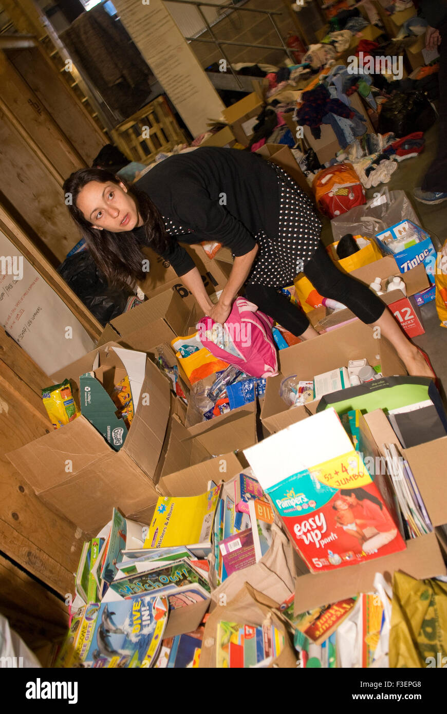 Volunteer in a shipping company's warehouse packing up donated items of clothing and other non-perishable items - Stock Image