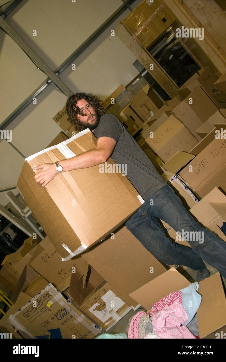 Volunteer in a removal company's warehouse moving packed up donated items of clothing and other non-perishable - Stock Image