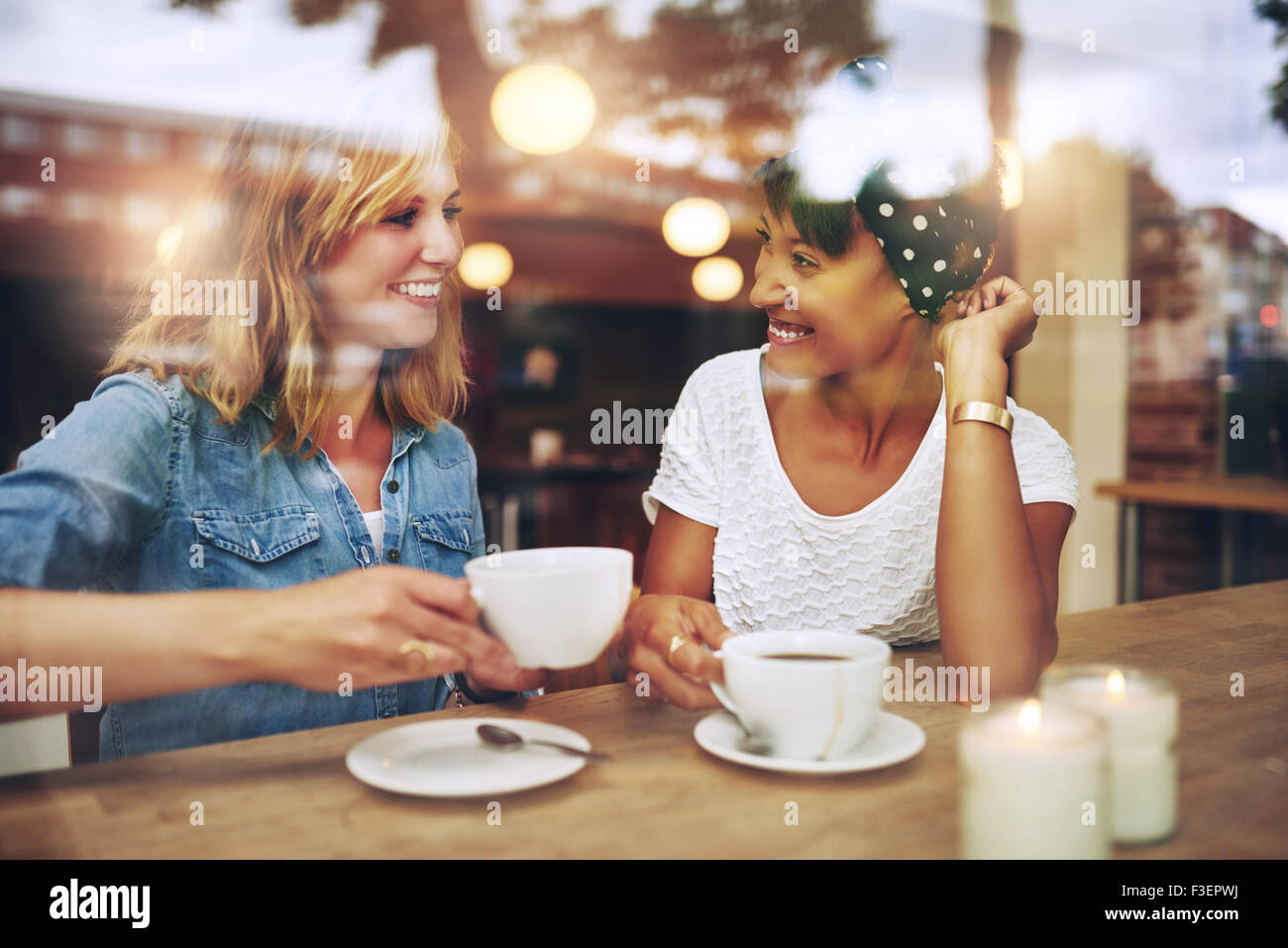 Two multi ethnic friends enjoying coffee together in a coffee shop viewed through glass with reflections as they sit at a table Stock Photo