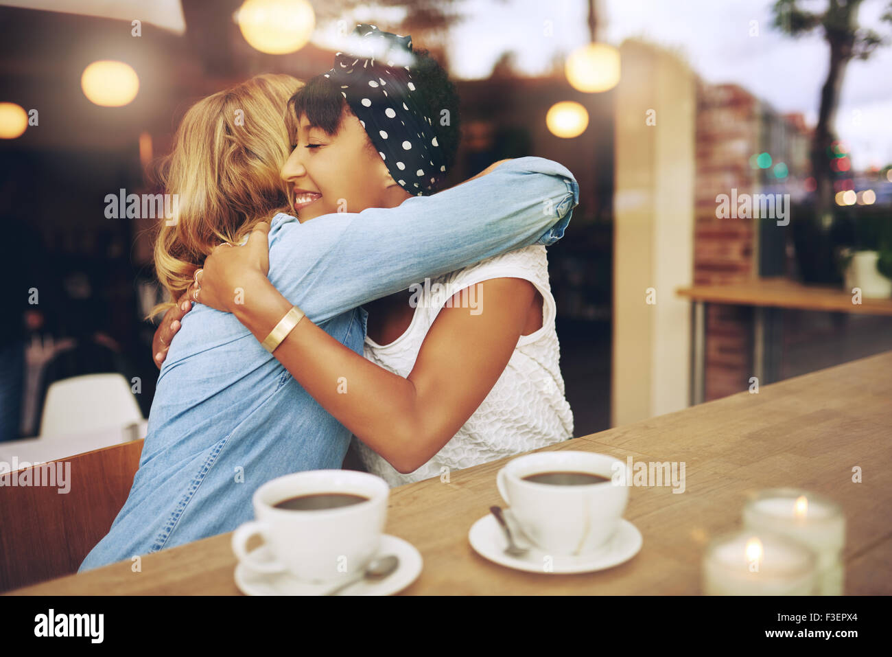 Two multi ethnic affectionate girl friends embracing as they sit in a coffee shop enjoying a cup of coffee together - Stock Image