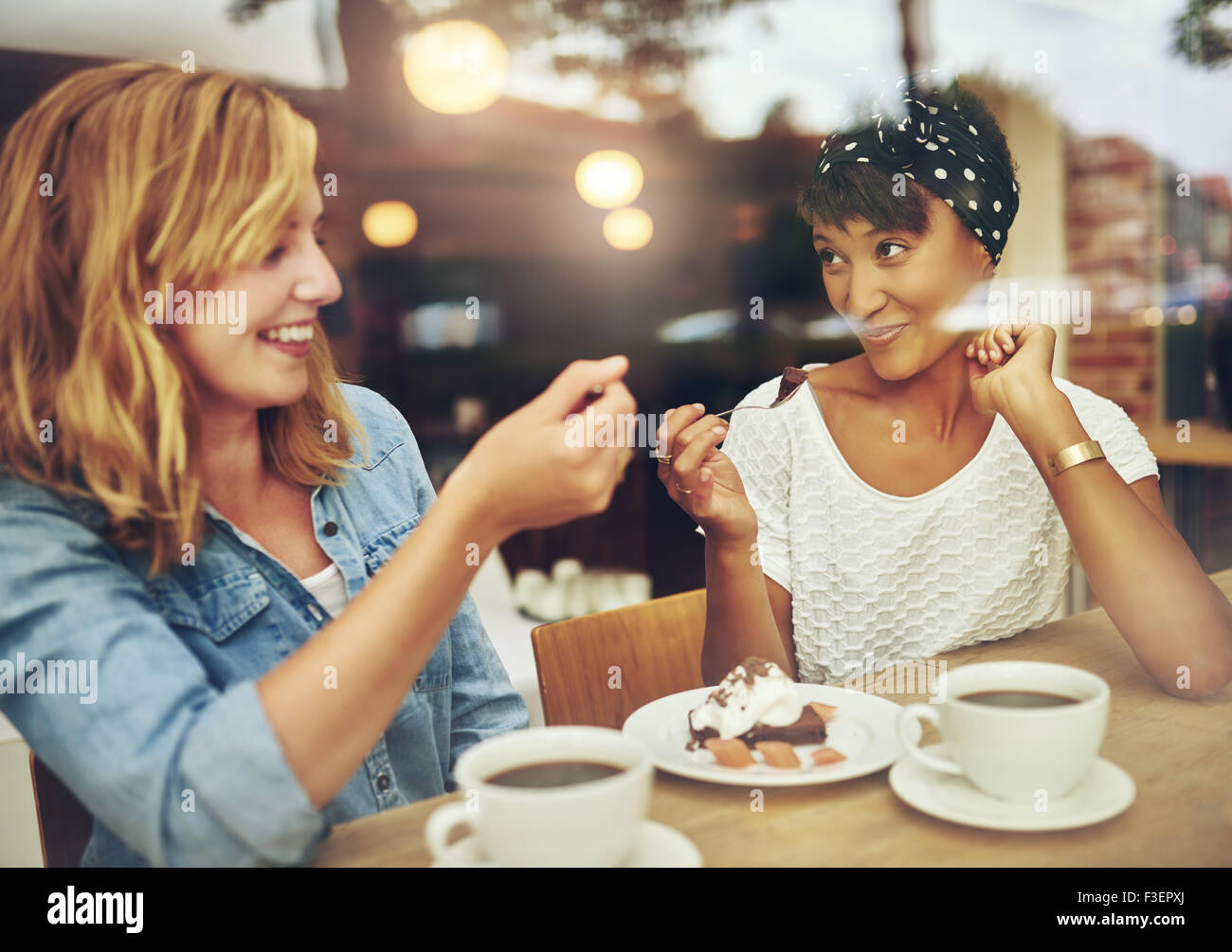 Two charismatic multi ethnic young girl friends sit at a counter in a cafe enjoying a cup of coffee while laughing - Stock Image