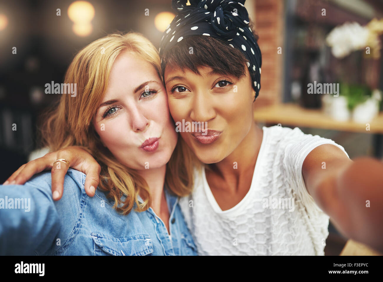 Two attractive playful young women standing arm in arm blowing a kiss at the camera puckering up their lips with - Stock Image