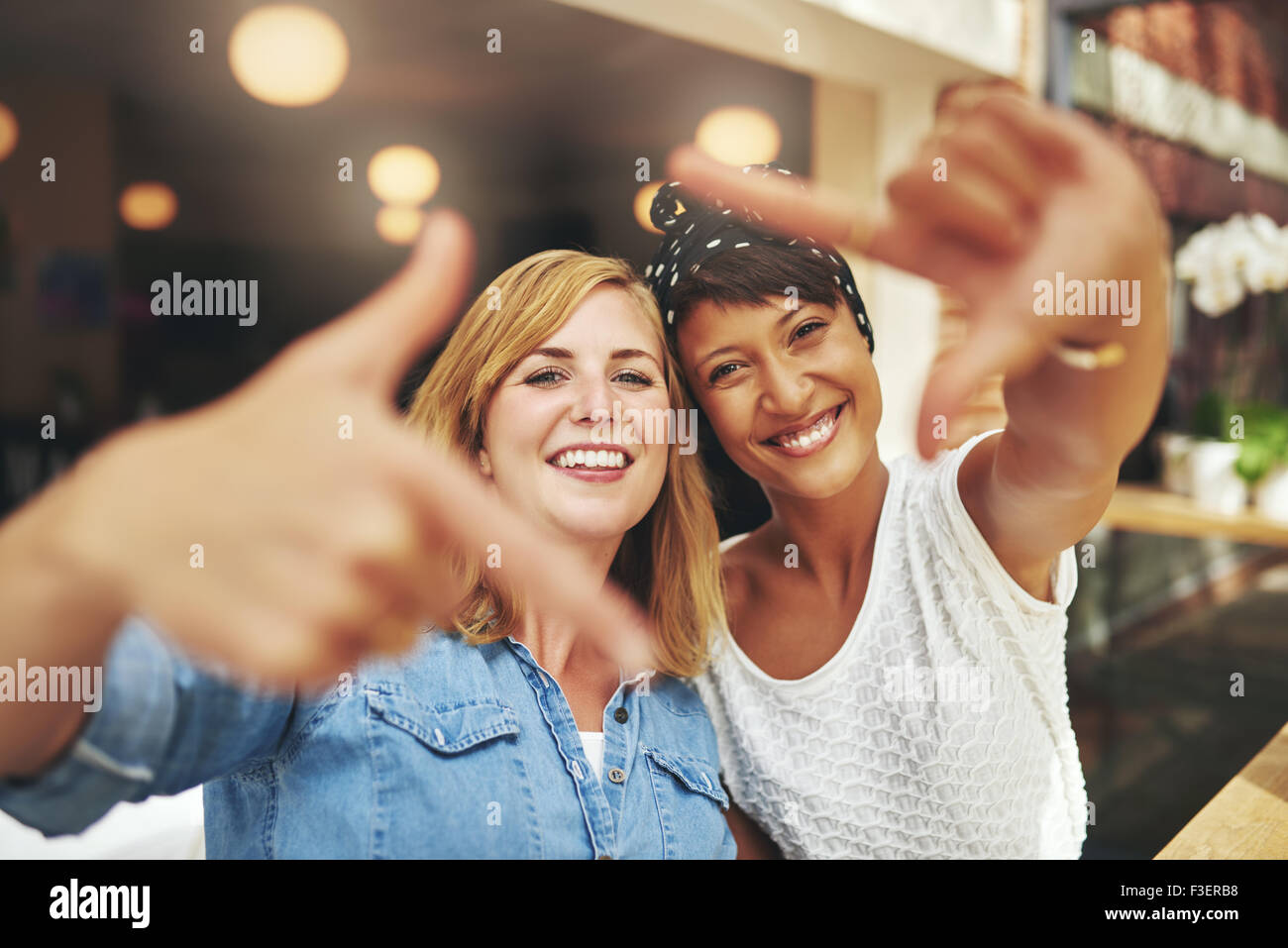 Vivacious young women framing their faces with a finger frame in a fun creative gesture as they sit in a cafeteria - Stock Image