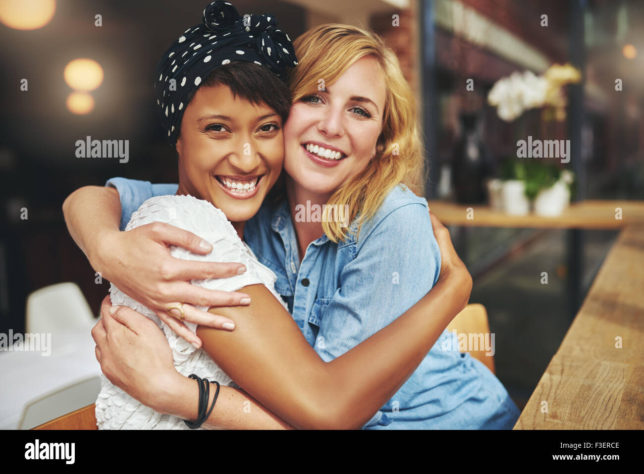 Two happy affectionate young woman hugging each other in a close embrace while laughing and smiling, young multiracial - Stock Image