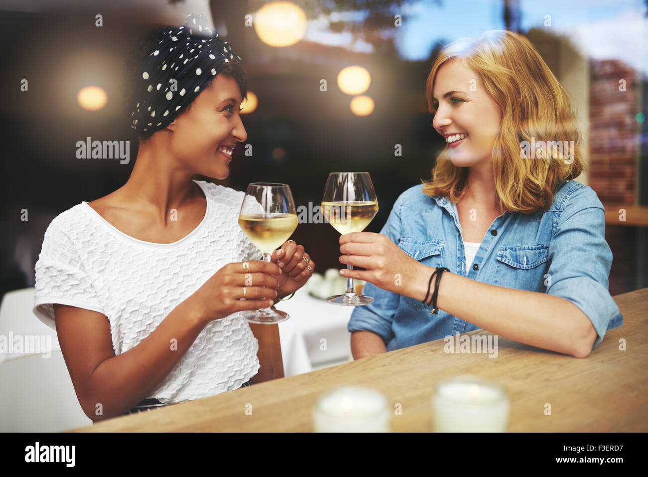 Pretty young women toasting each other with glasses of white wine as they meet up in a pub for a relaxing chat - Stock Image
