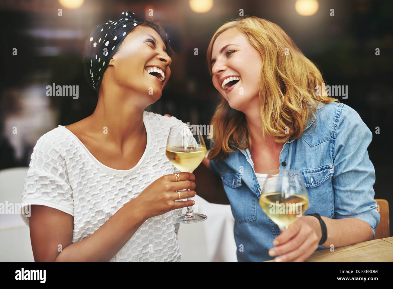 Two young attractive vivacious multiethnic female friends celebrating and laughing together over a glass of white - Stock Image