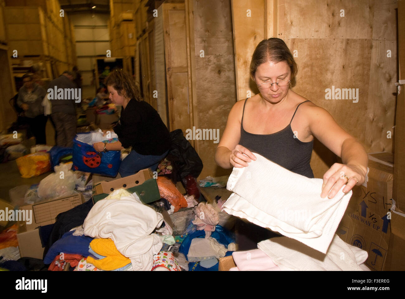 Volunteer in a removal company's warehouse packing up donated items of clothing and other non-perishable items - Stock Image