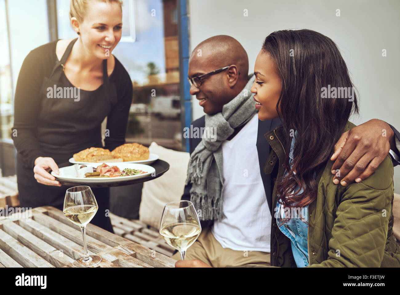 Waitress serving food to an affectionate African American couple sitting arm in arm at a restaurant table - Stock Image