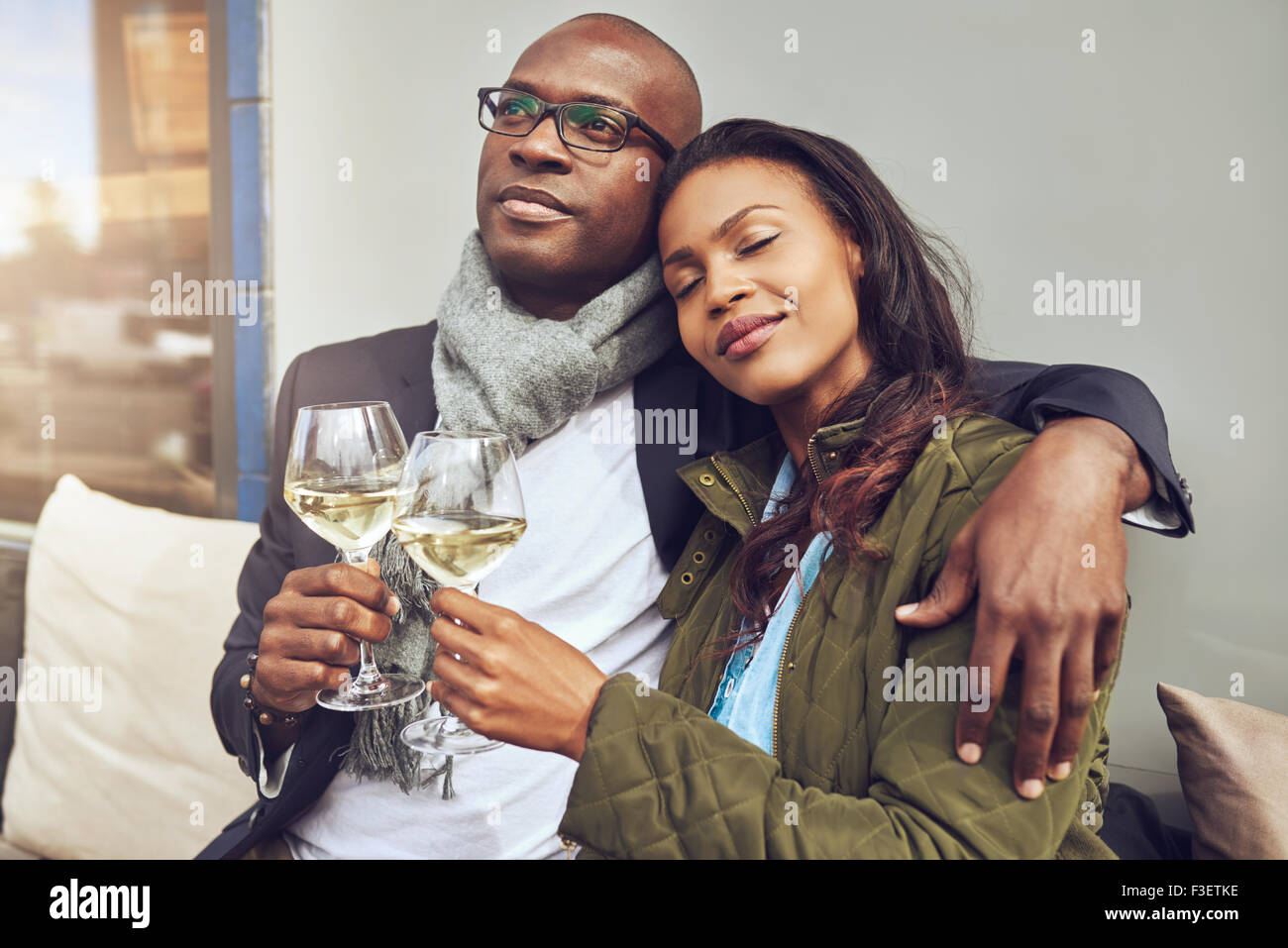 Blissful romantic young African couple relaxing in each others arms while enjoying a drink of white wine at a restaurant - Stock Image
