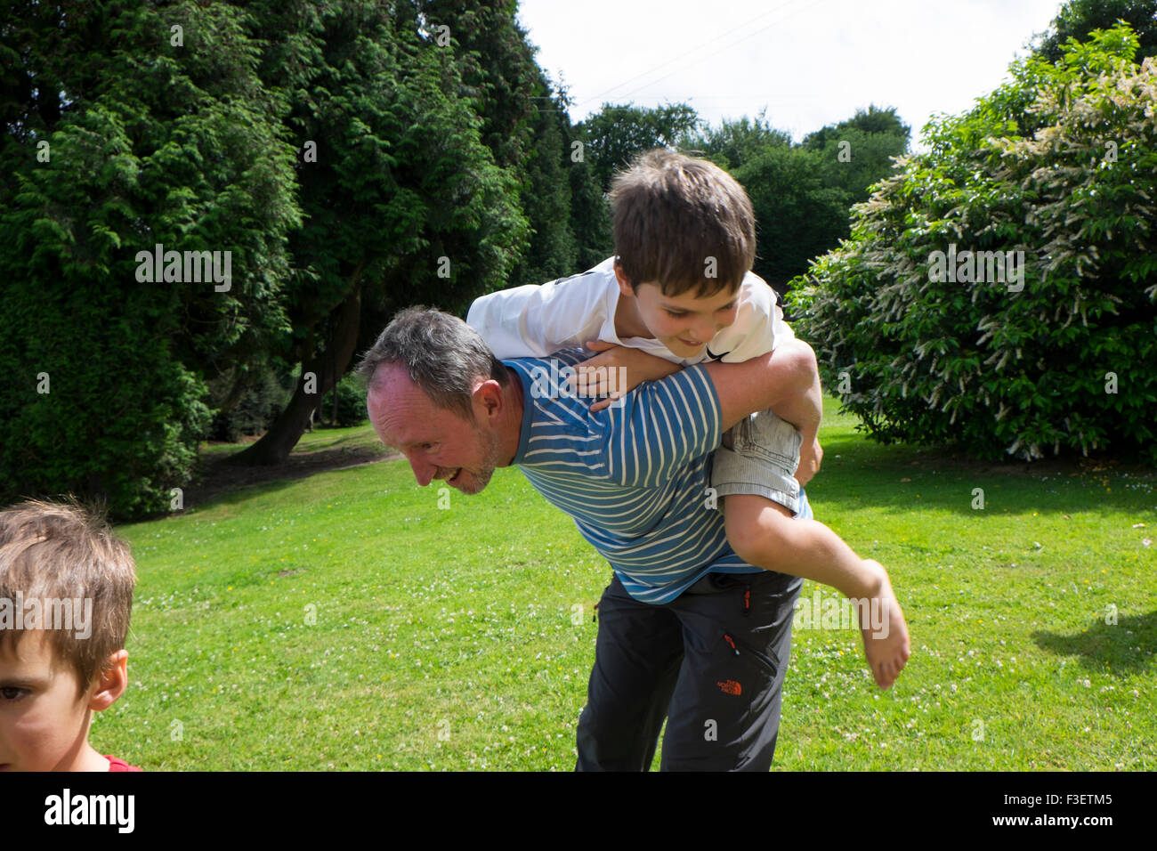 50 year old man playing with 8 year old nephew in garden, Monmouth, Powys, England, UK - Stock Image