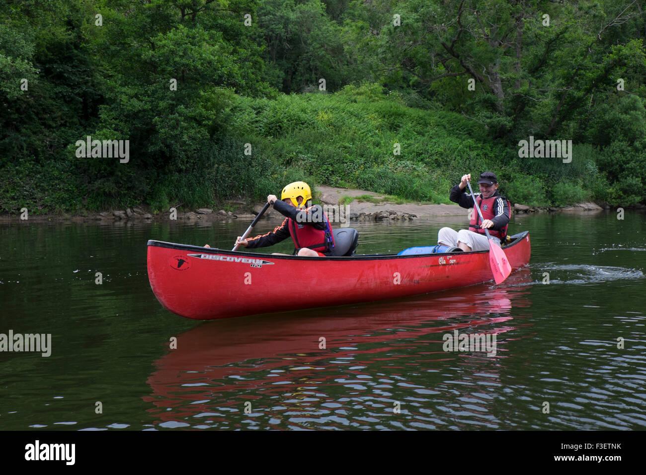 Father with 8 year old son paddling kayak canoe on River Wye near Symonds Yat, Herefordshire, England, UK - Stock Image