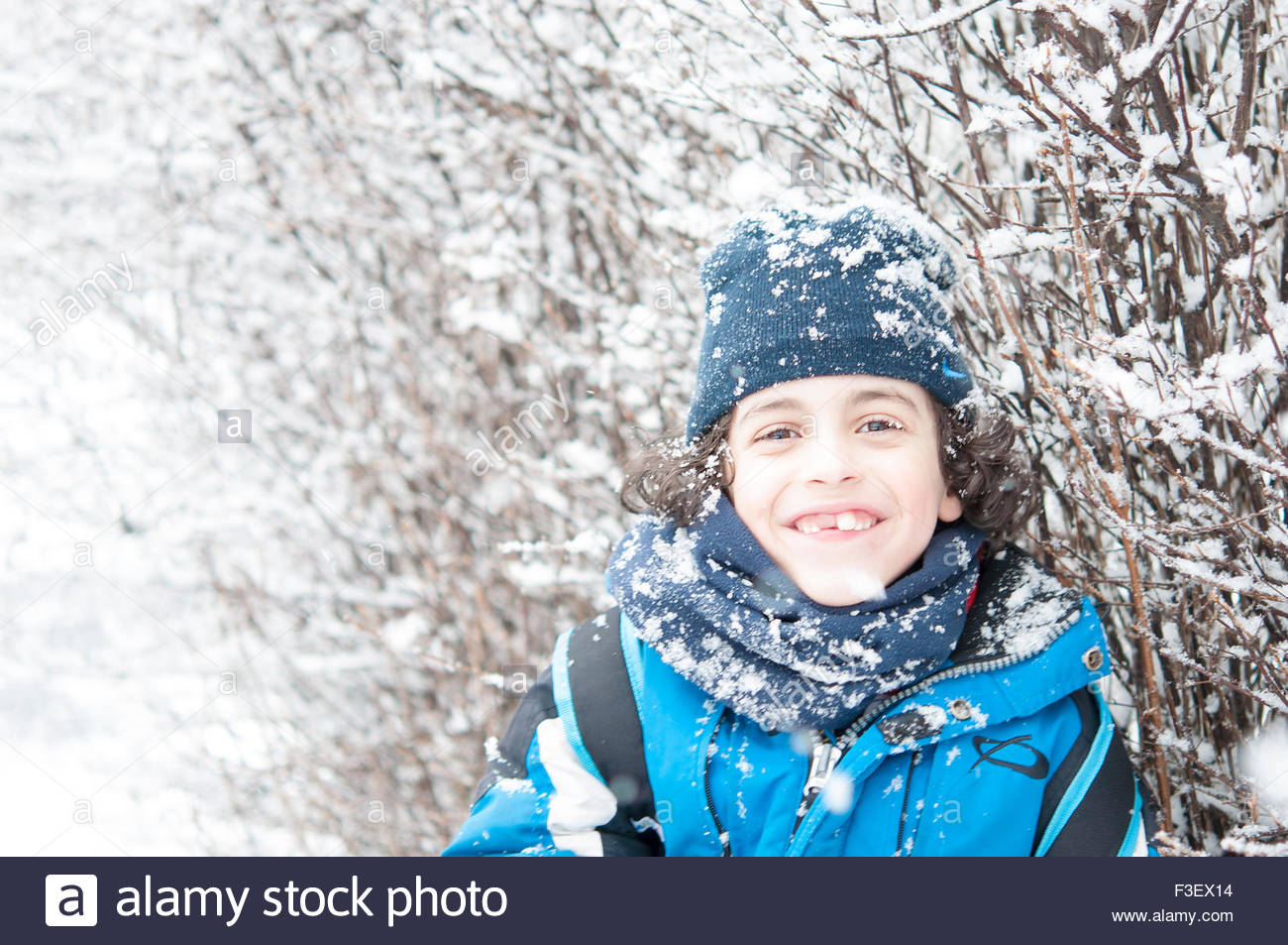 Boy standing in snow and enjoying the Canadian Winter.  He is wearing a thick blue jacket, black pants, black gloves, - Stock Image