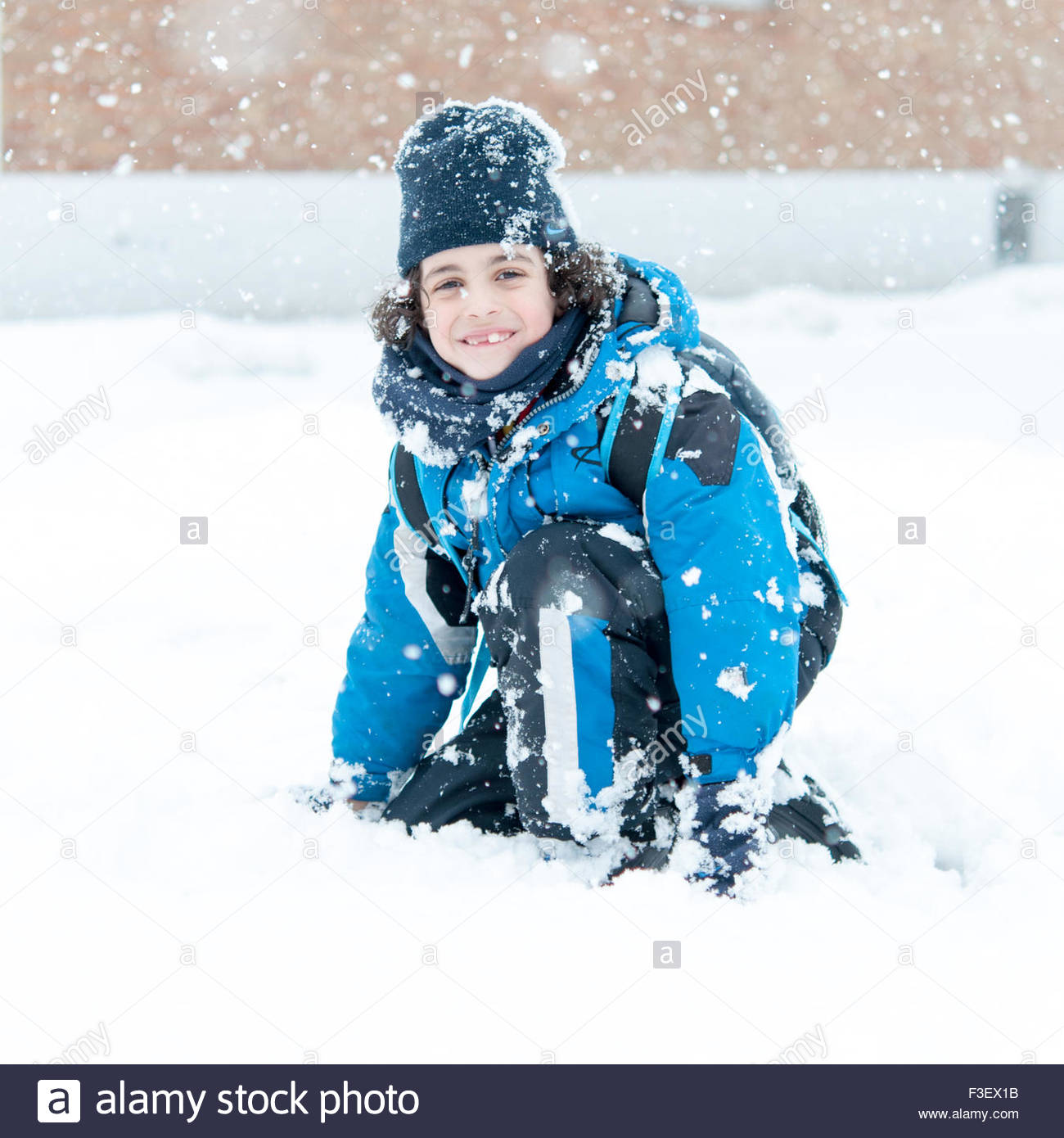 Boy sitting in snow  and enjoying the Canadian Winter.  He is wearing a thick blue jacket, black pants, black gloves, - Stock Image