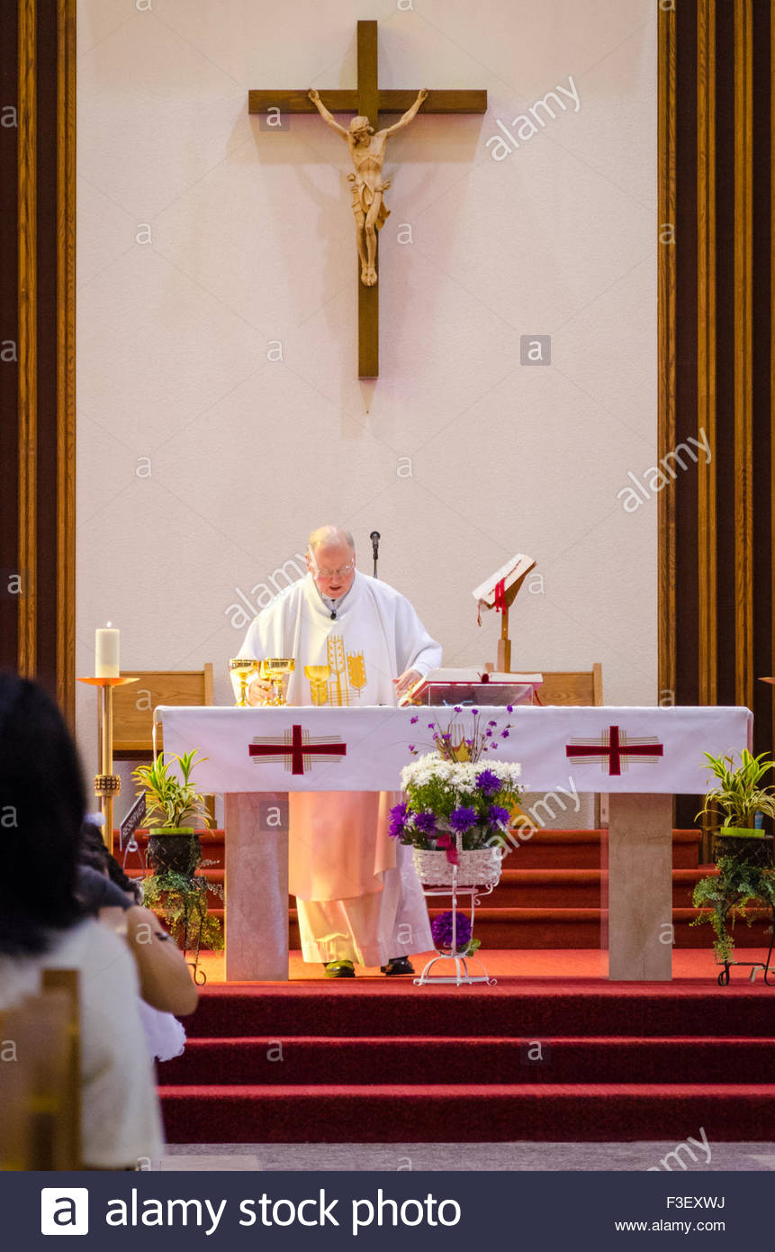 Catholic Priest At Altar In Church He Is An Elderly Man In White Stock Photo Alamy