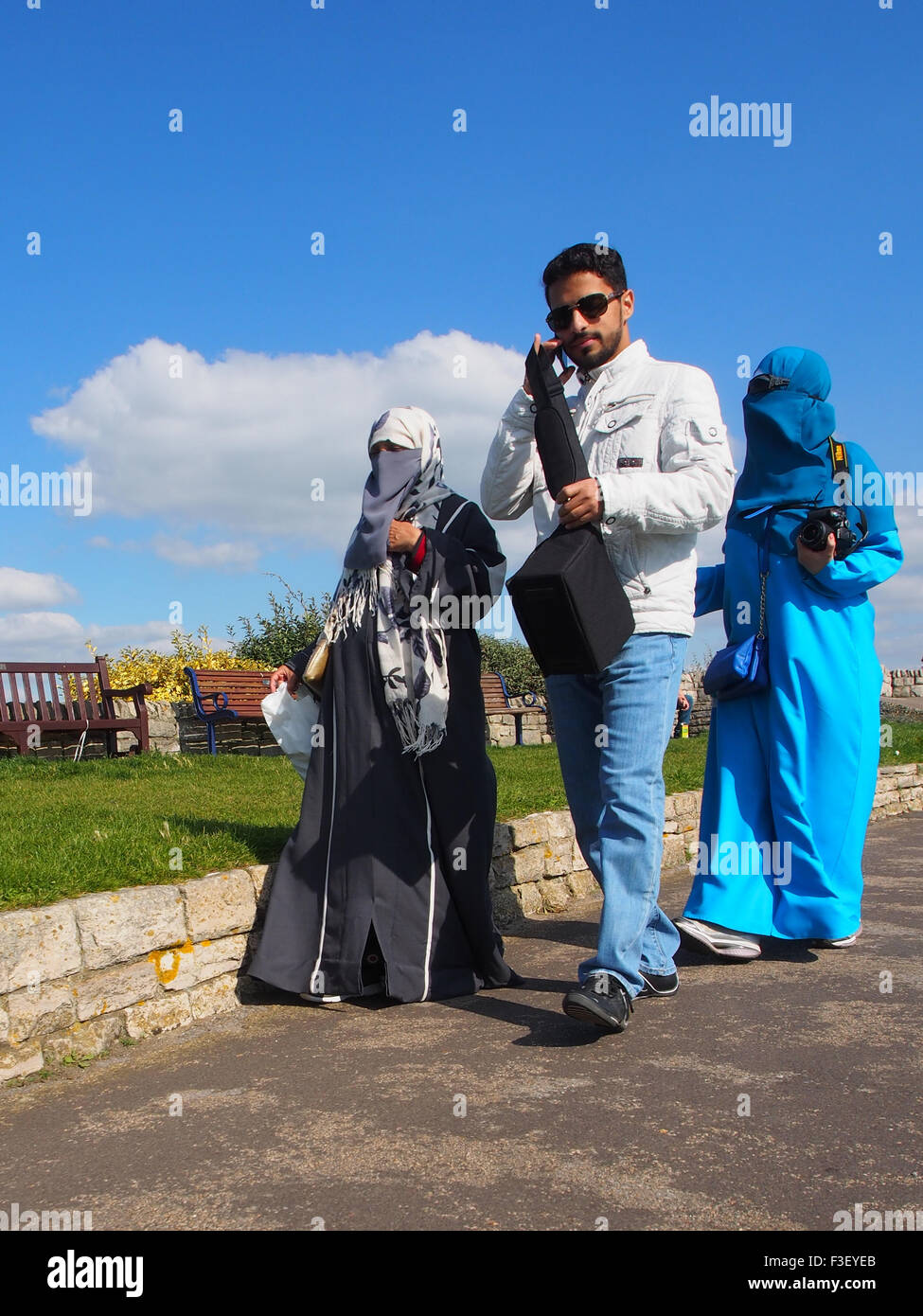 A muslim male in western clothes and two females wearing traditional Niqabs - Stock Image