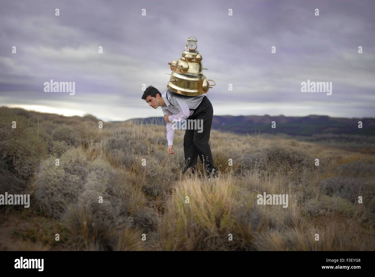 Conceptual boy man supporting the weight of time on his back big clocks on his back stormy sky sadness feeling old - Stock Image