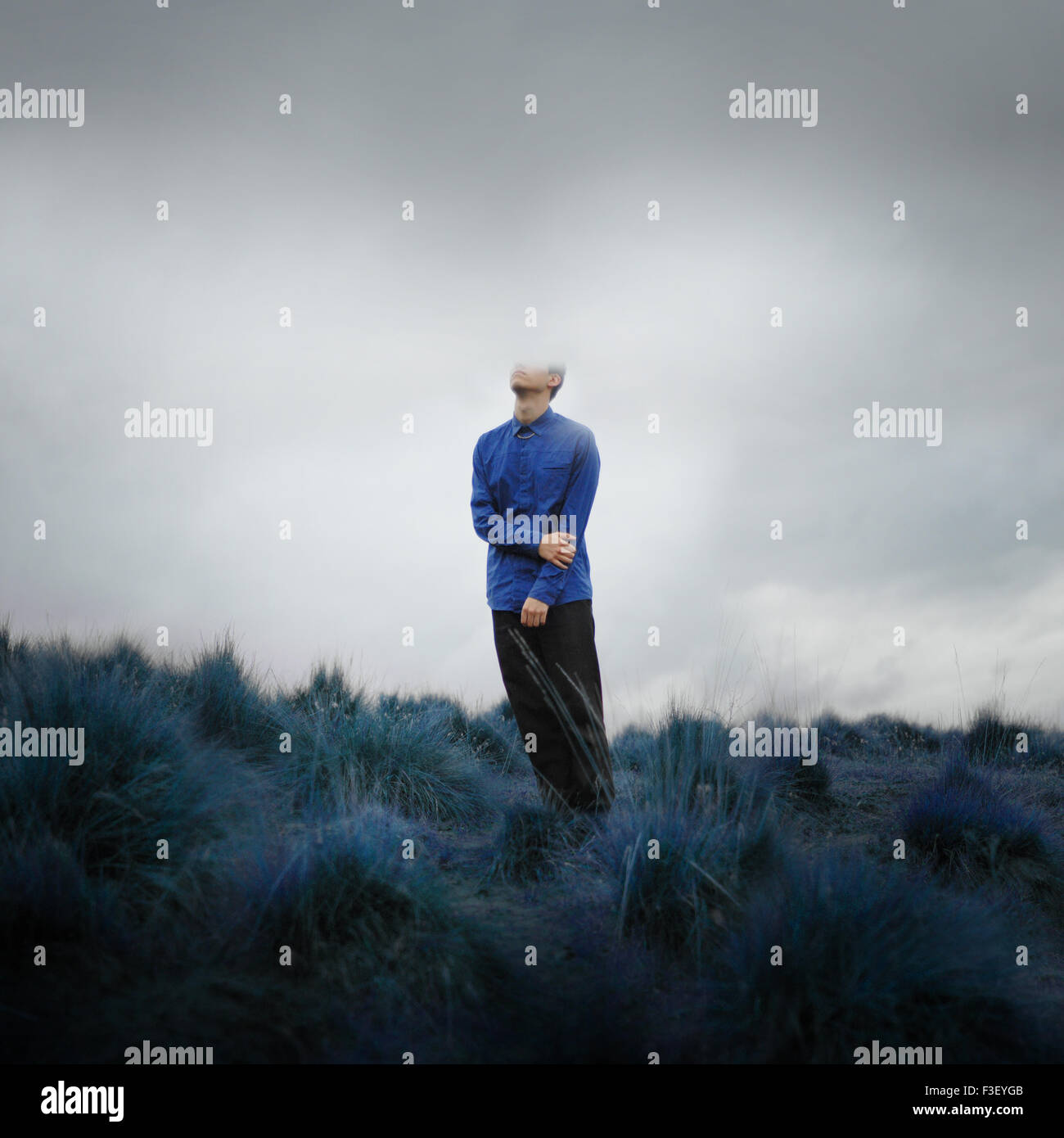 Boy blue shirt with the head in the clouds cold day blue stormy sky - Stock Image