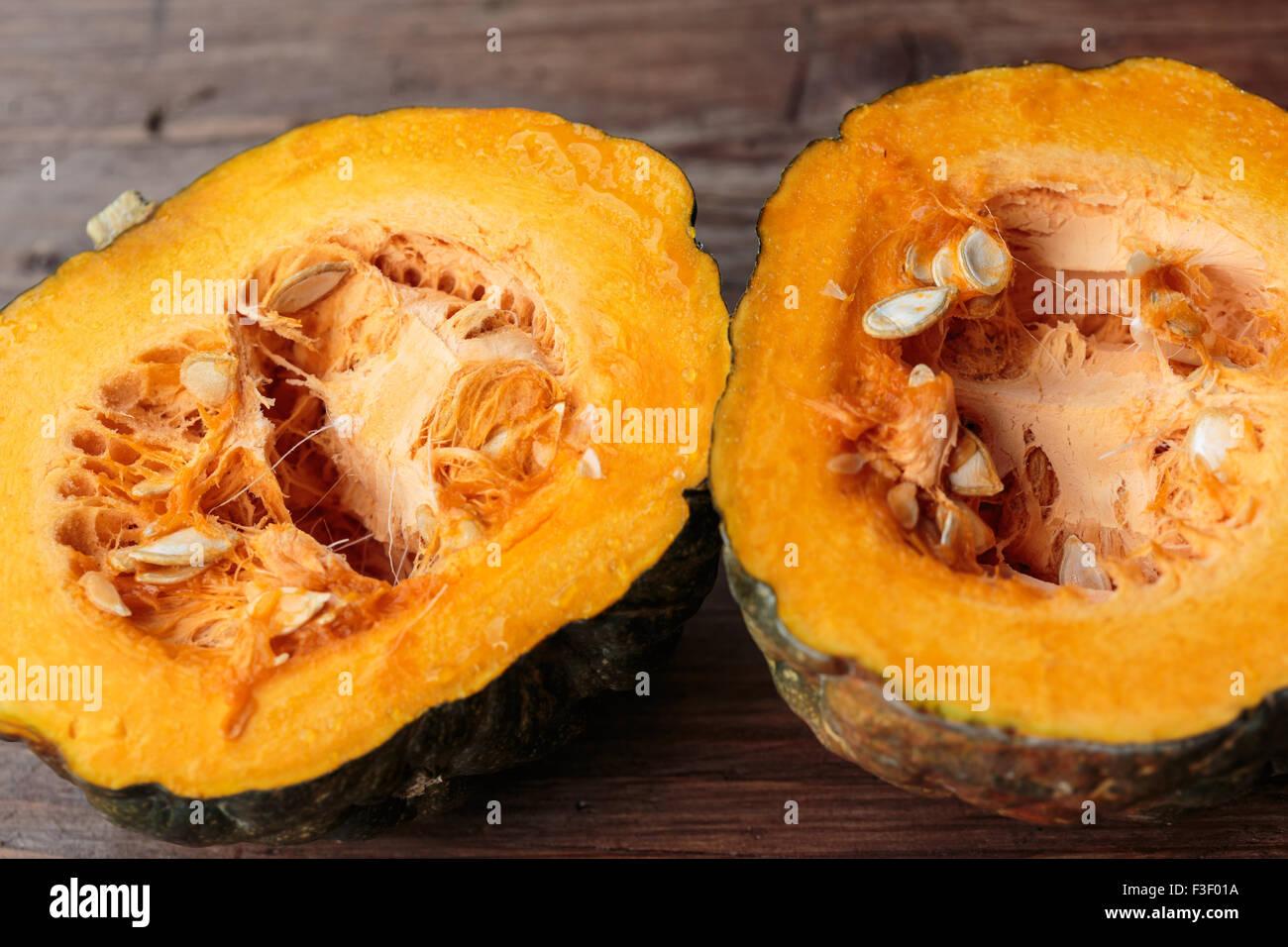 Halved pumpkin on wooden table - Stock Image