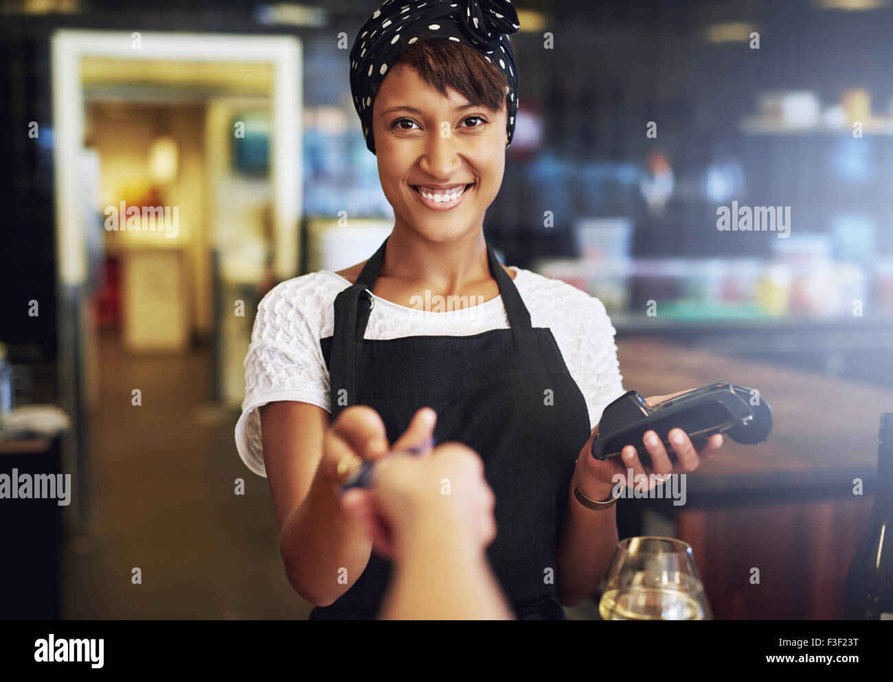 Smiling waitress or small business owner taking a credit card from a customer to process through the banking machine - Stock Image