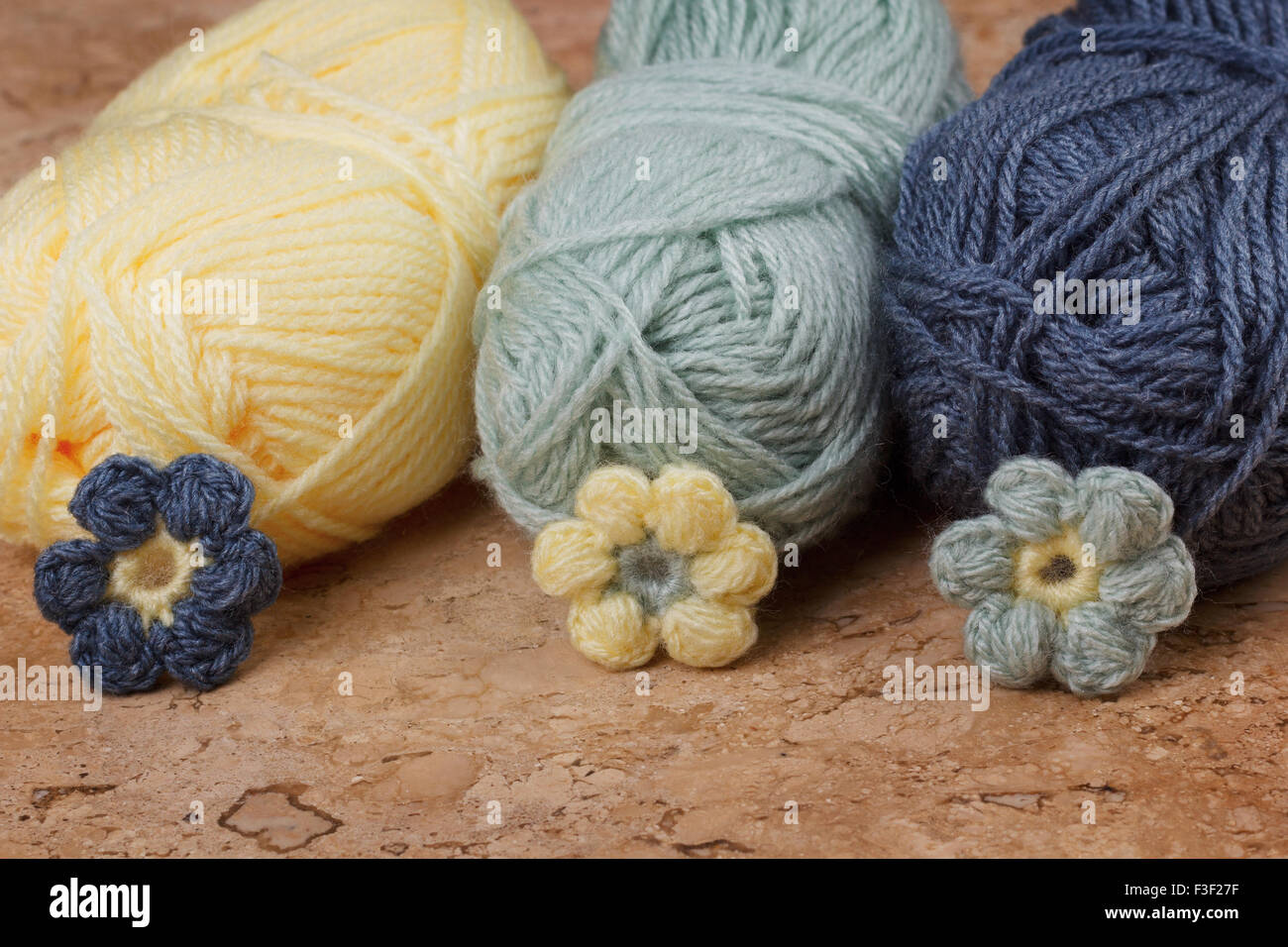 Handmade colorful crochet flower with skein on marble table. Selective focus - Stock Image
