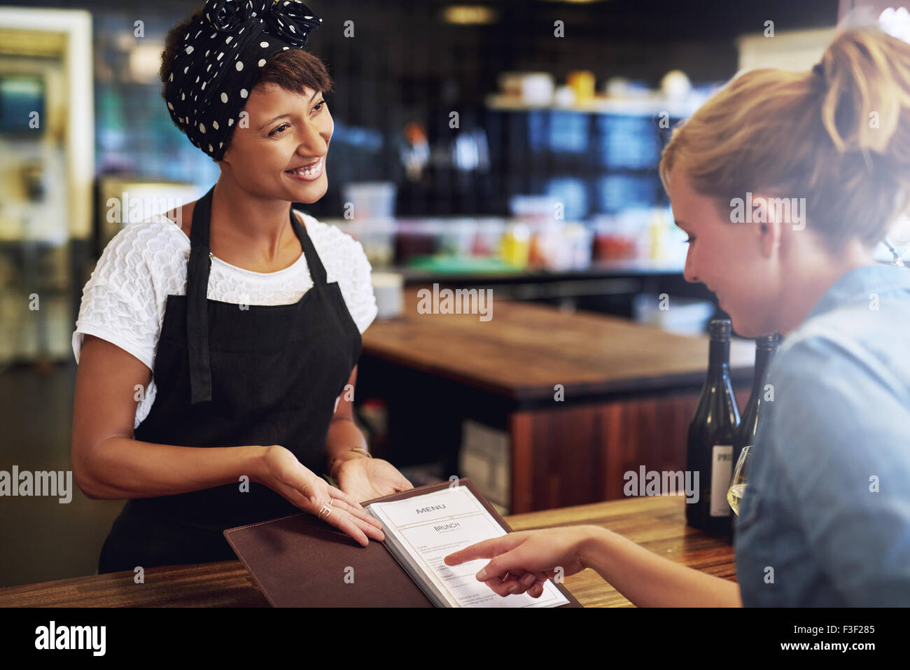 Customer checking a wine menu in a pub being presented to her by an attractive friendly young African American small - Stock Image