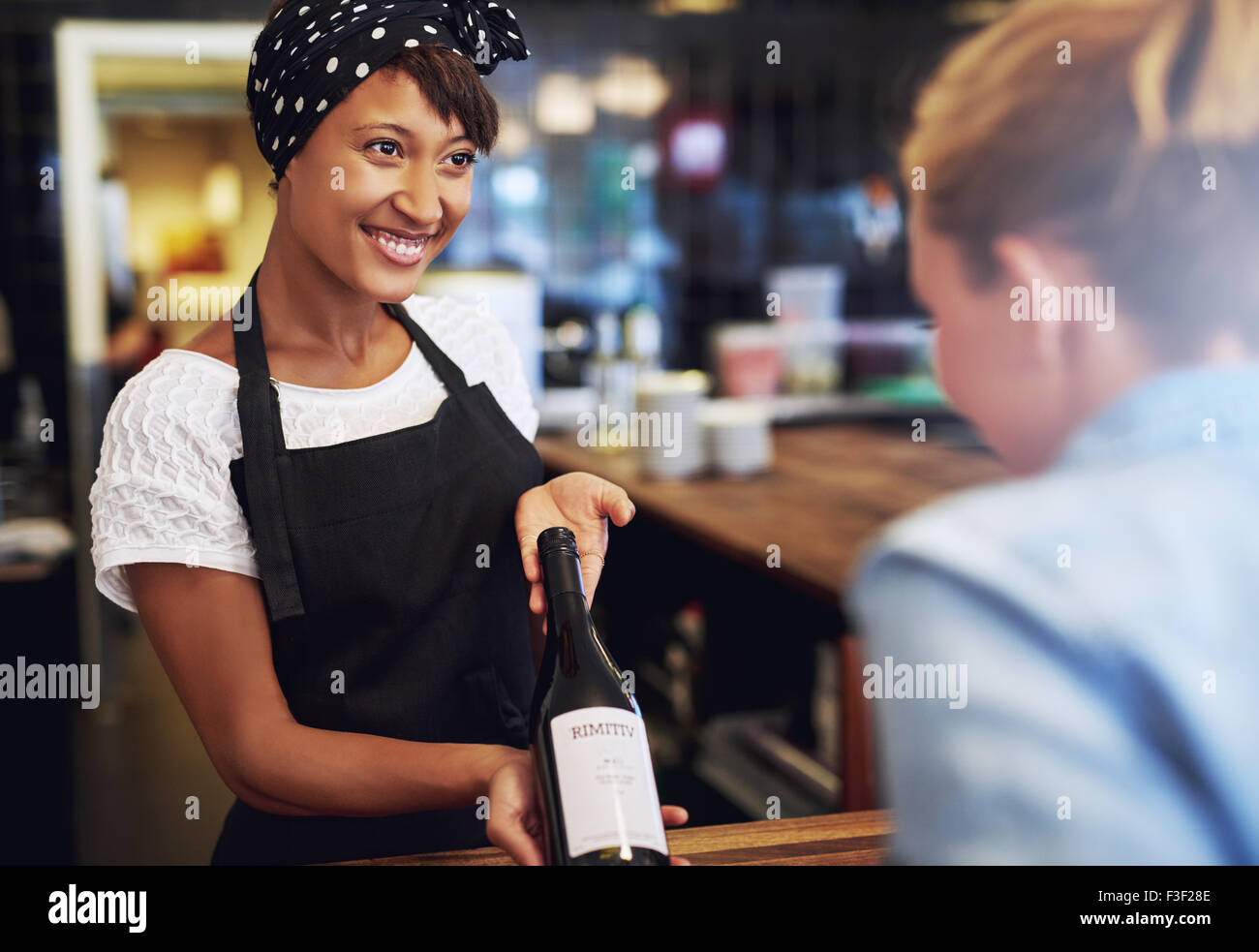 Smiling attractive young African American waitress or bartender showing a bottle of red wine to a customer in a - Stock Image