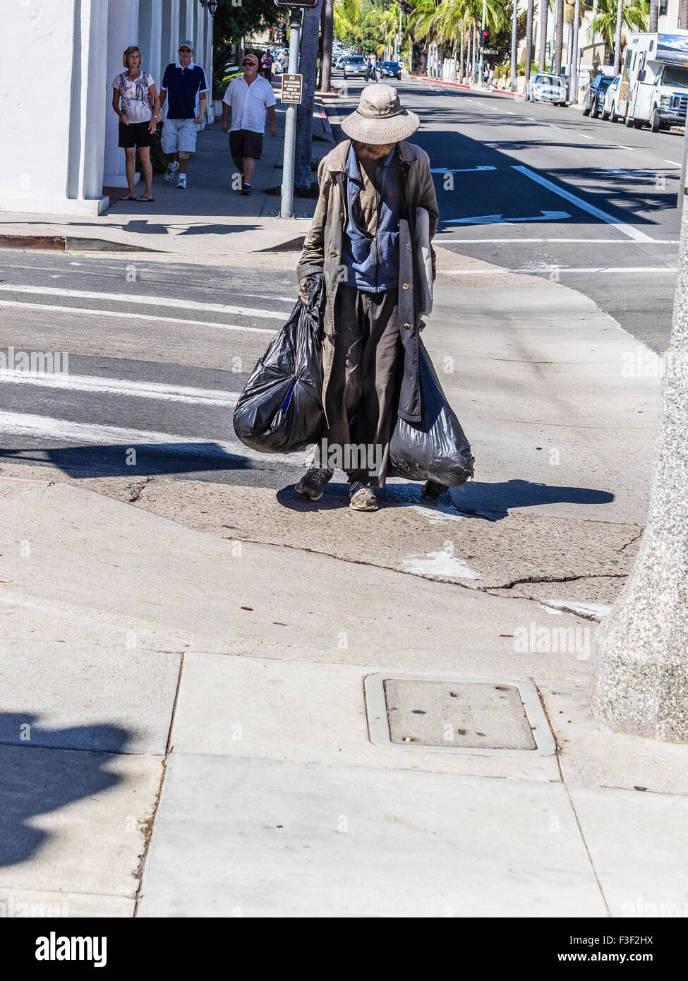 An older adult homeless man wearing a long coat and a hat on a hot day and carrying two large black plastic garbage - Stock Image