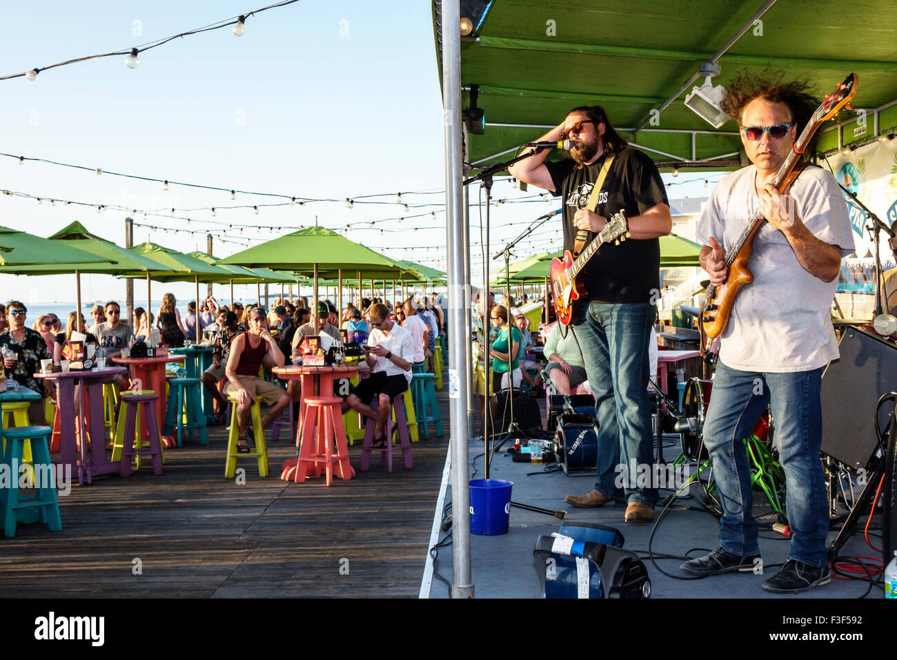 Key West Florida Keys Sunset Pier bar restaurant stage live music musician man band playing guitar audience Stock Photo