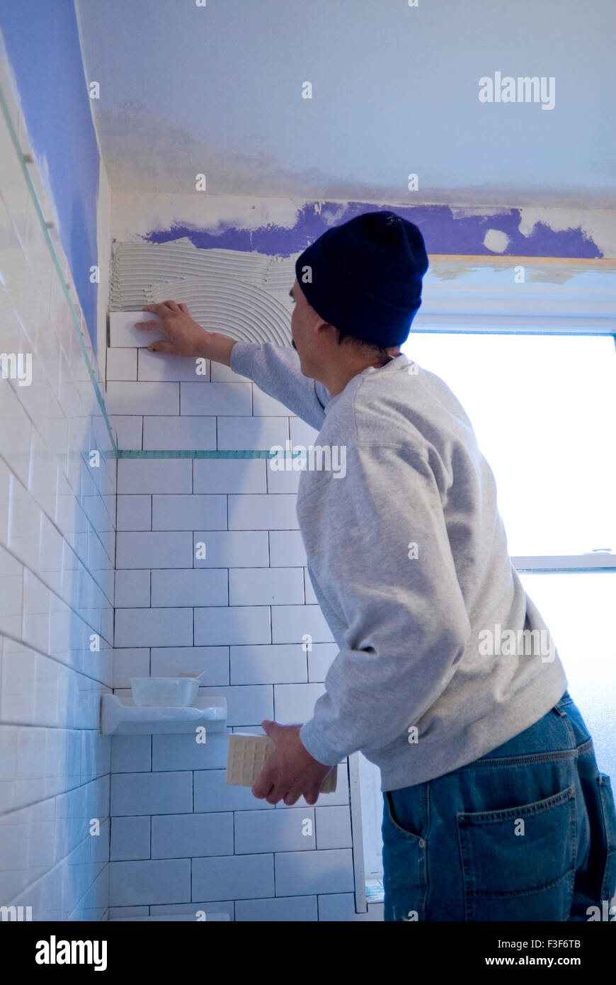 Mexican man tiling a bathroom wall with subway tiles Stock Photo ...