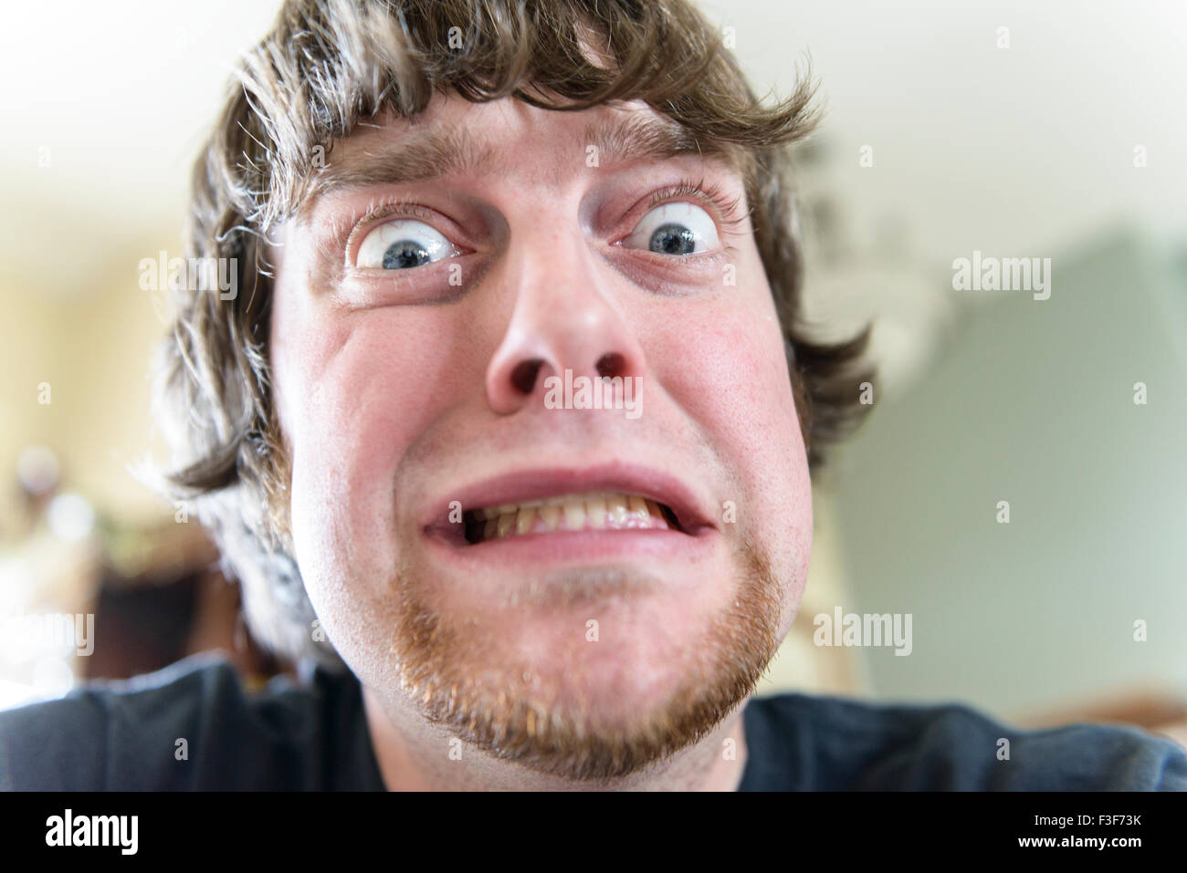 A young Caucasian man in his mid-20s makes a funny face with bulging eyes. Closeup. USA. - Stock Image