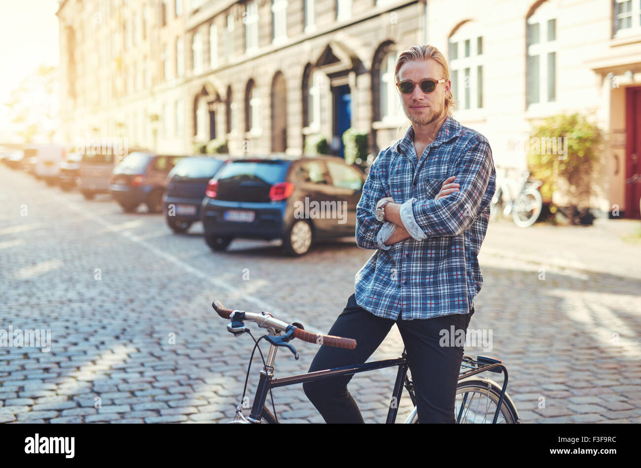 Portrait of man on his bike with arms crossed looking stylish. City lifestyle - Stock Image