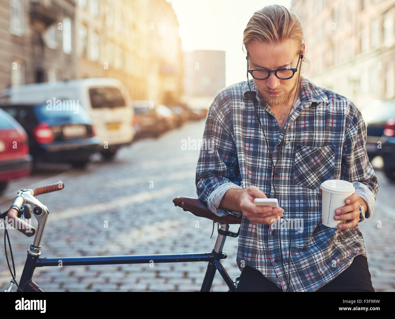 Outdoor portrait of modern young man with mobile phone in the street, sitting on bike - Stock Image