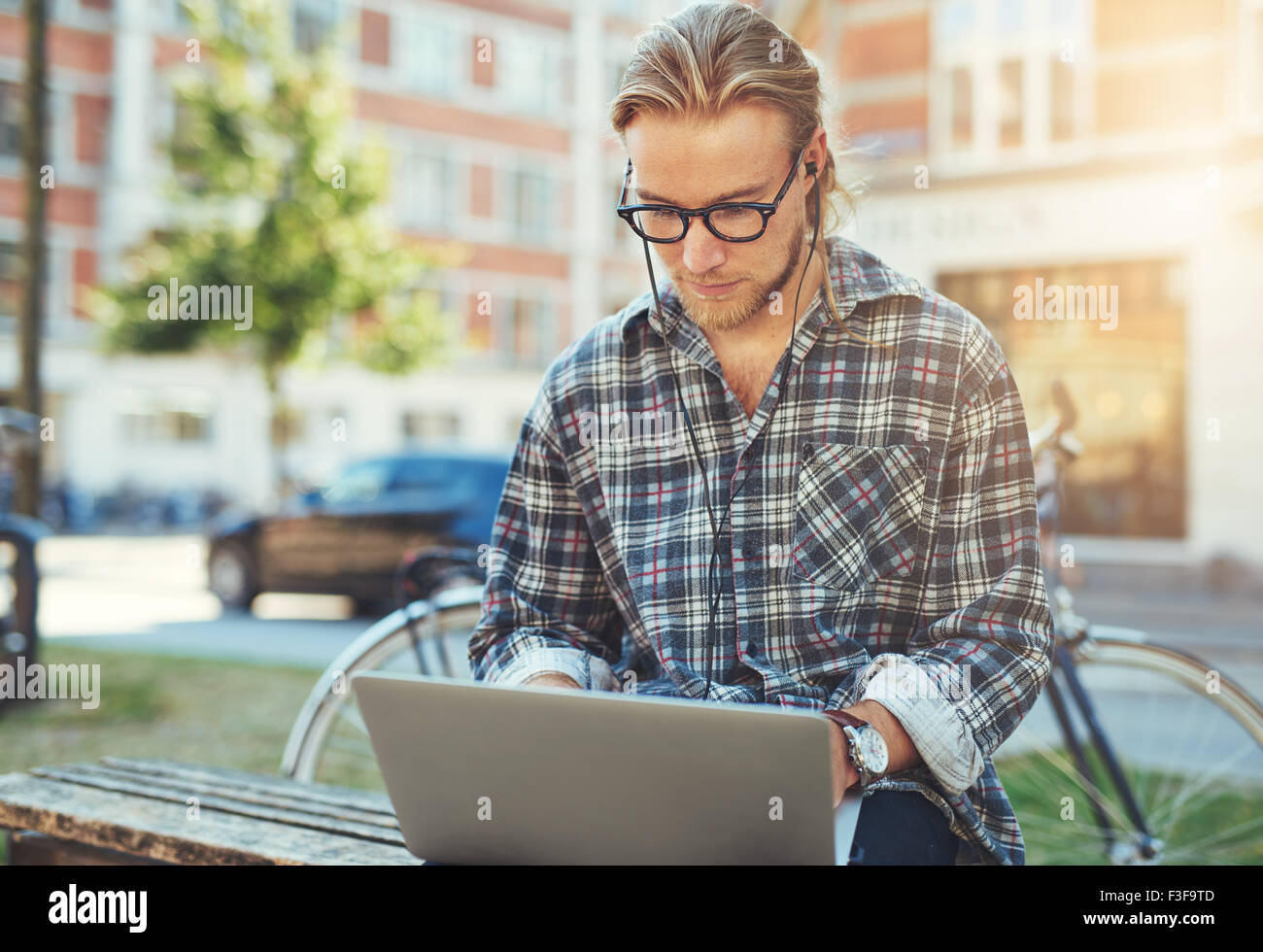 Concentrated young man with his laptop, sitting outside working - Stock Image