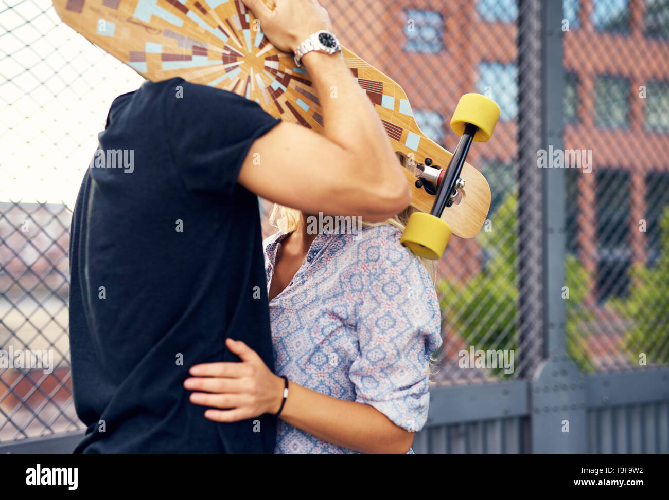 caressing couple hiding behind skateboard and kissing Stock Photo