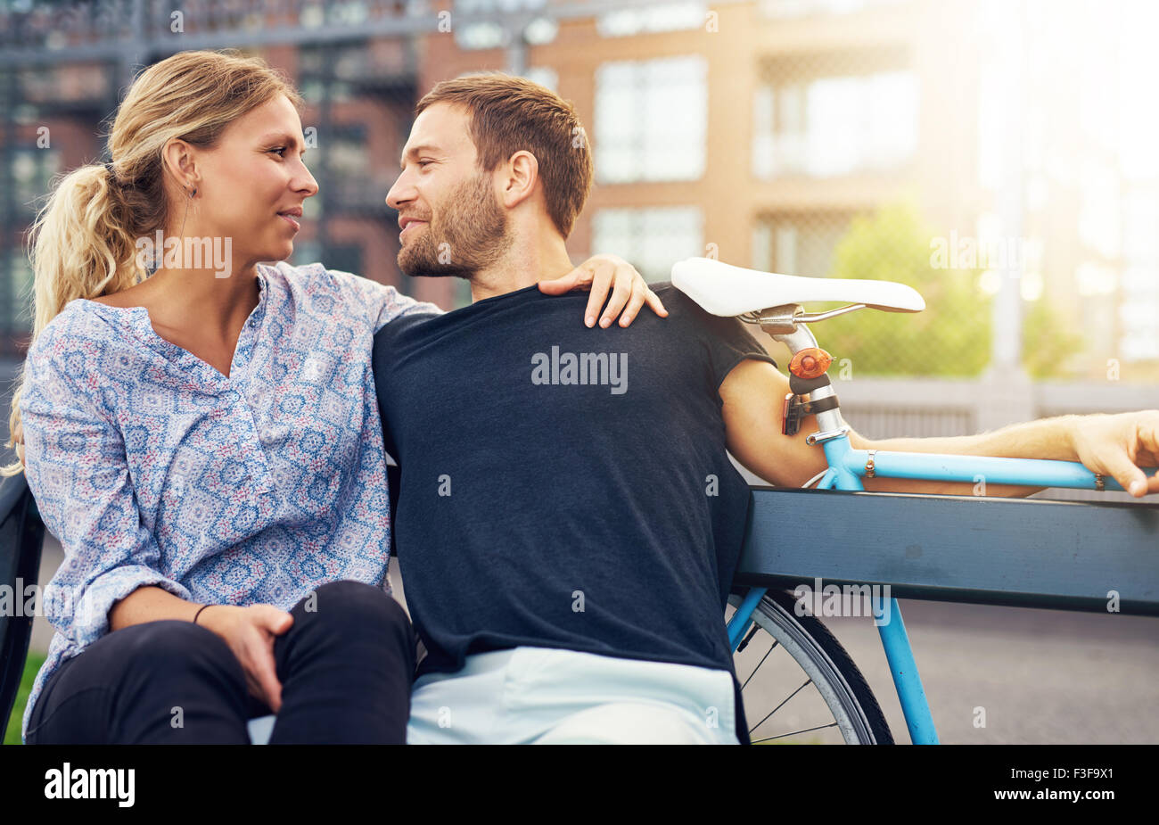 Loving couple sitting on bench in a city environment - Stock Image